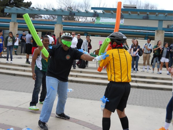 Two lunch activity participants battle with foam noodles on Athletes vs. Mathletes day.