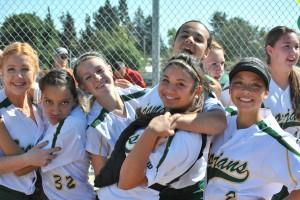The girls varsity softball team smiles amidst its loss. Photo by Adrianna Vandiver.