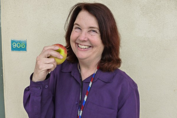 Pat Parker smiles with an apple, the symbol of education and teaching. Photo by Tyler Macias.