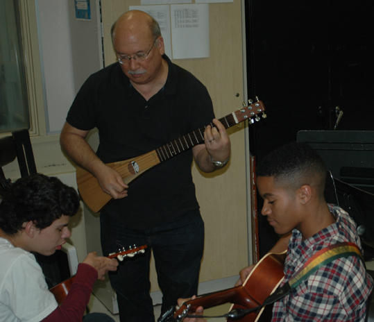 Guitar teacher Steve Wilkinson shares a musical moment with Ben Barraza and Sean Luster. Photo by Caitlin Forbes.